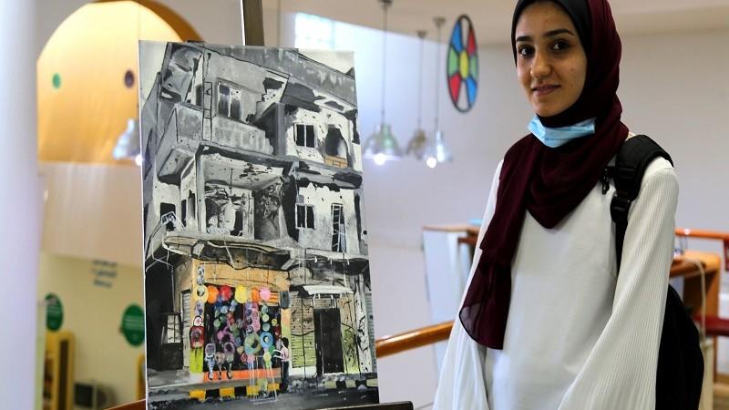 وعد البياري (16 عاماً) تقف بجانب رسمة رسمتها ضمن مشاركتها في نادي الرسام الصغير